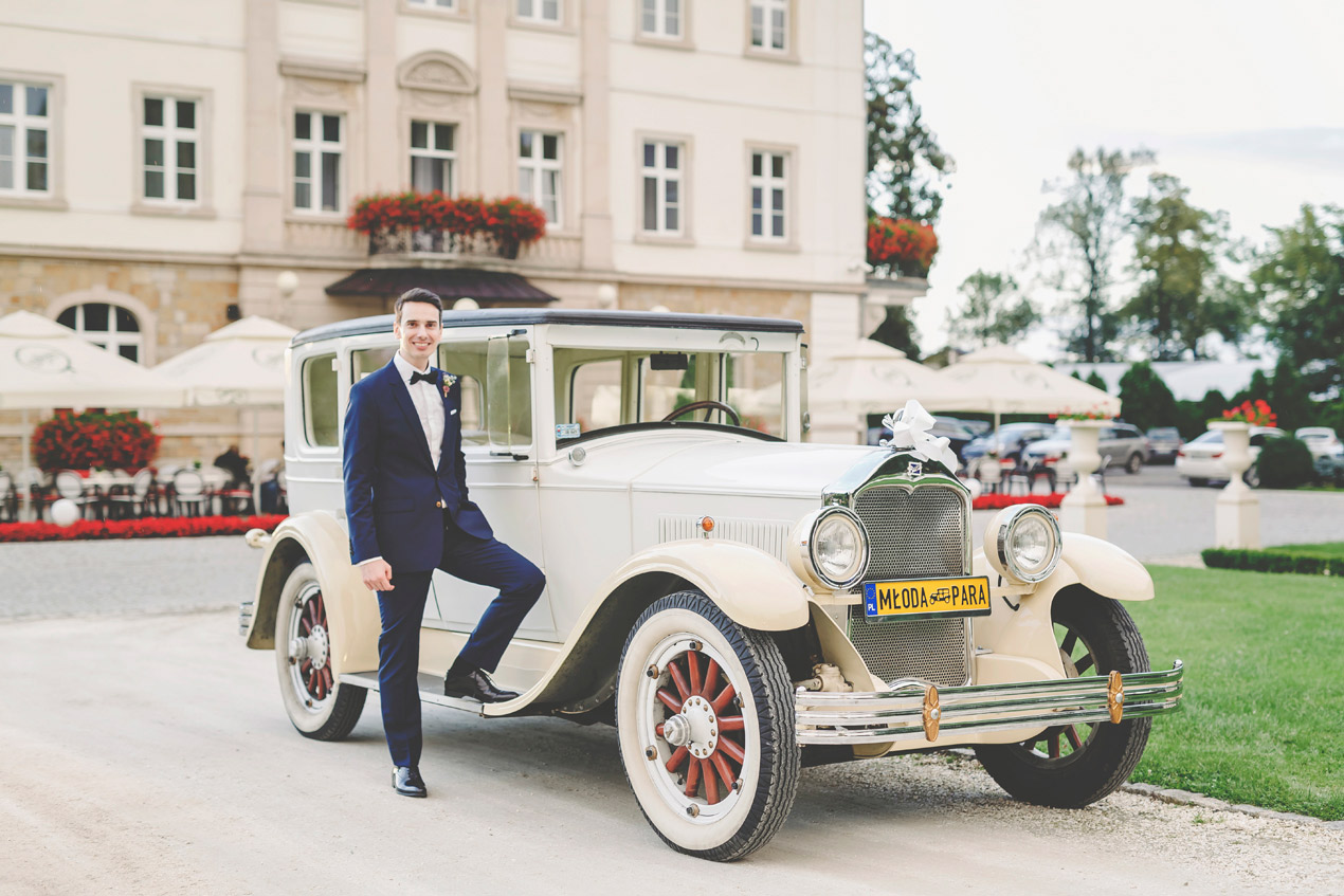 ślub w pałacu,Pałac Brunów, slub, wesele, pan młody przy samochodzie, buick, retro samochód